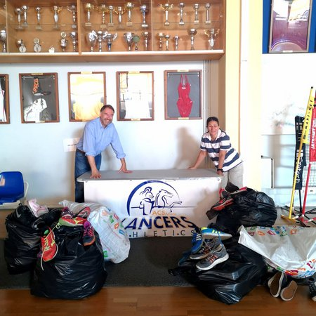 Mrs. Annie Constantinides, the ACS Athens Athletic Director and Mr. Kazantzopoulos, the President of the Institute Team of the World with the collected sports shoes.